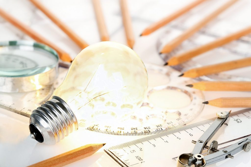lit light bulb with rulers and pencils on desk